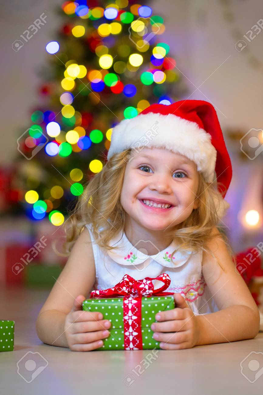 96aef57552740 little girl in Santa hat holding a present under the Christmas tree Stock  Photo - 91522331