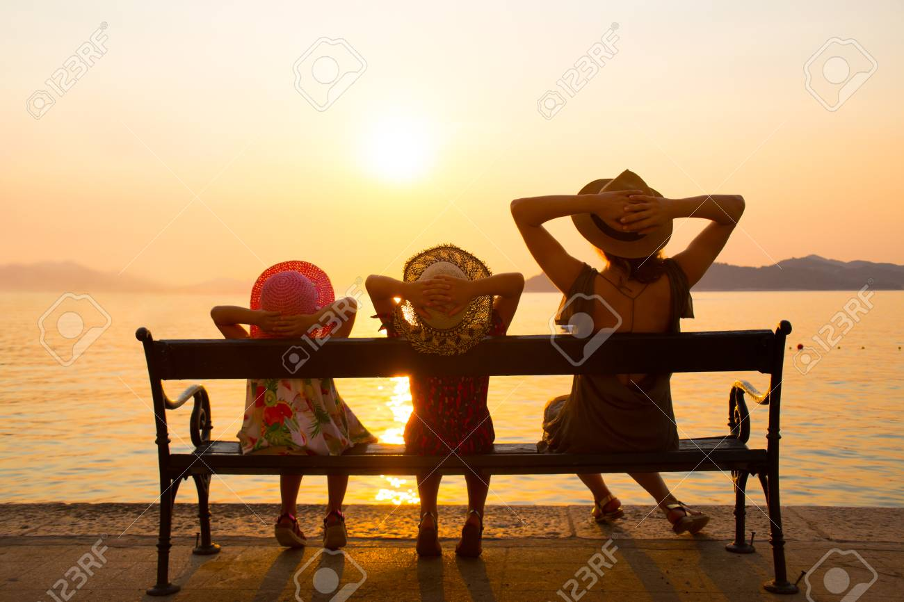 Family With Children Sitting On A Bench On The Seafront At Sunset