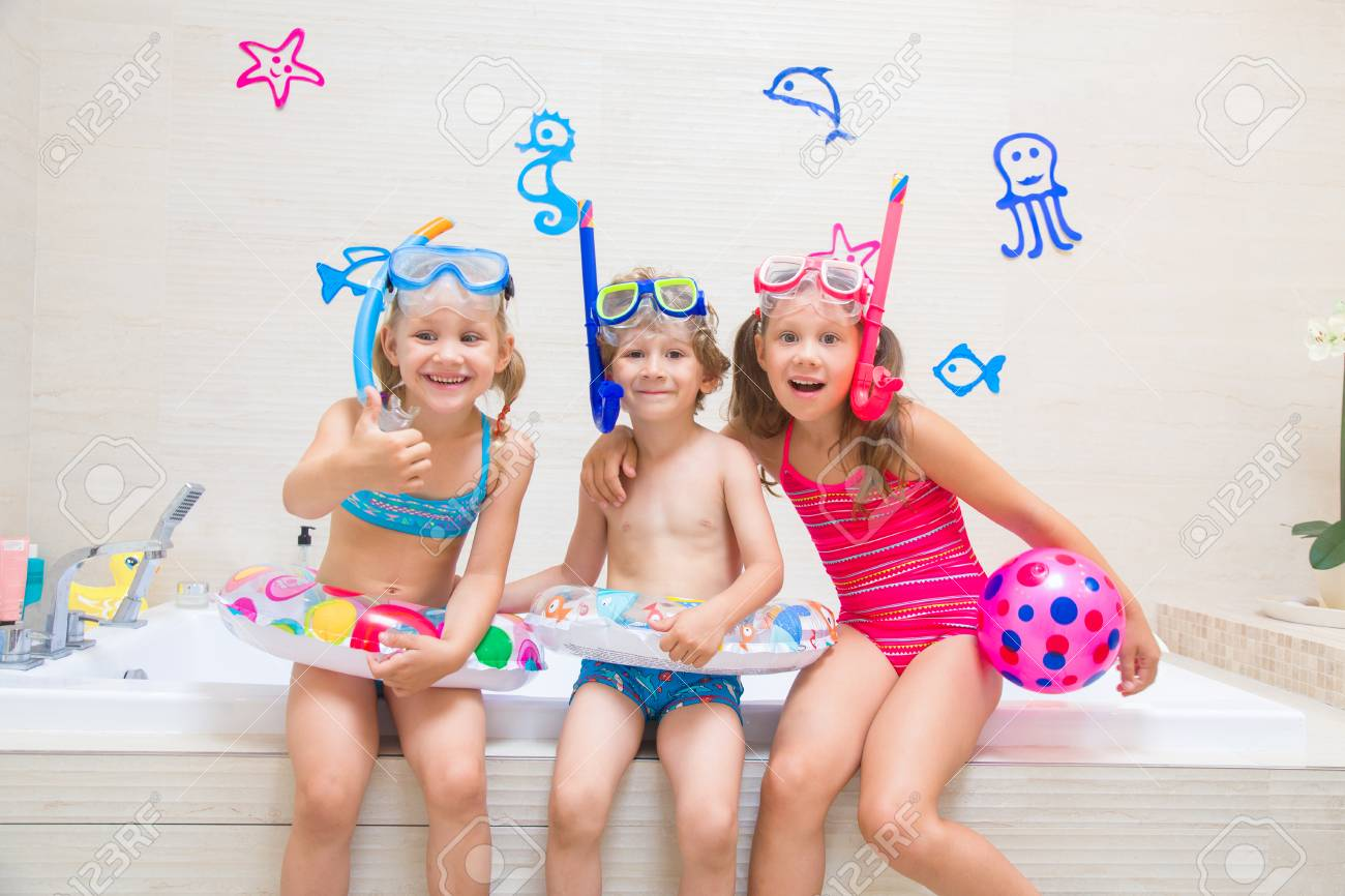 2cc881c81edf7 Little children in swimsuits and diving equipmen play in the bathroom like  in the sea Stock