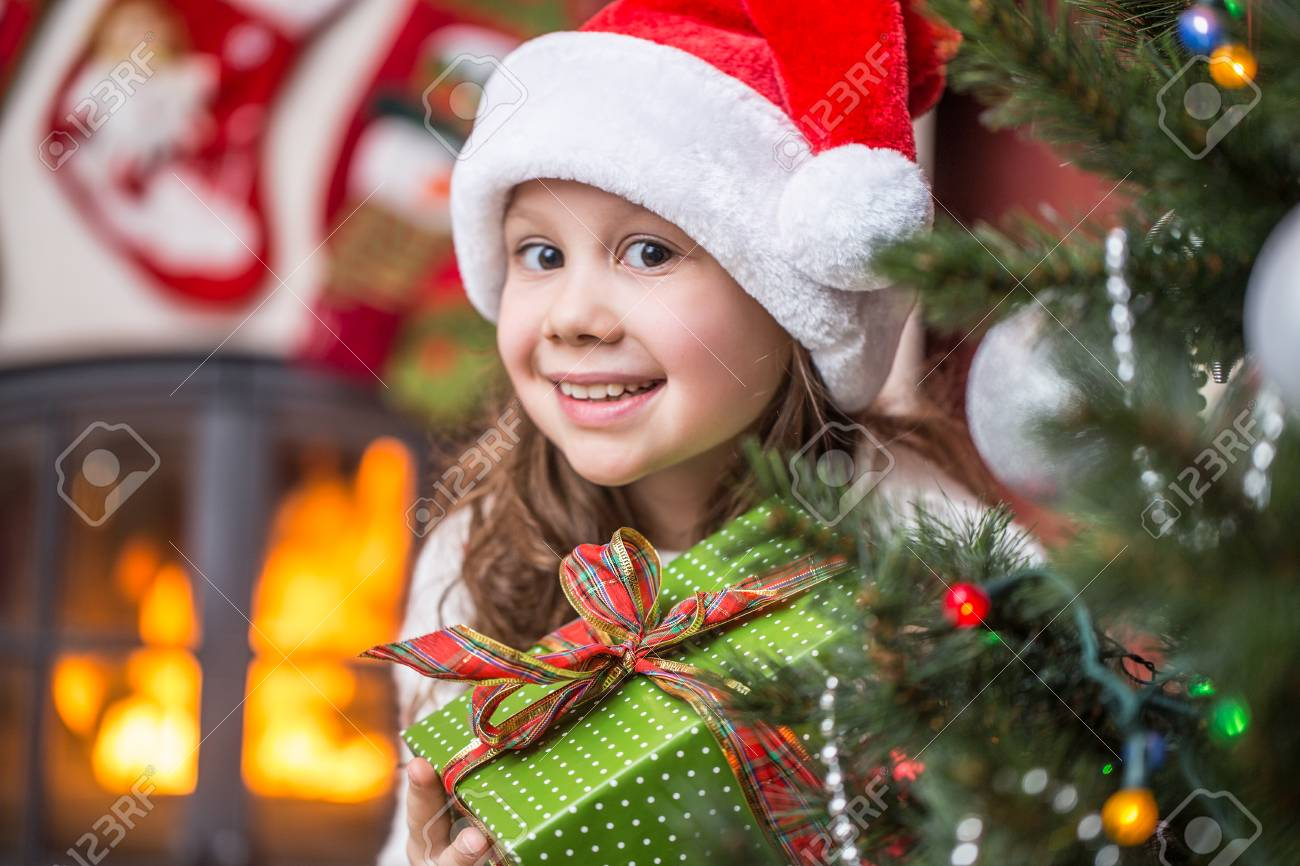 bfded33459db1 little girl in Santa Claus Hat with presents on Christmas party Stock Photo  - 115503640