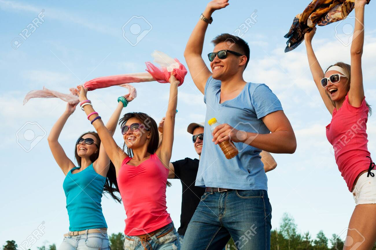 group of happy young people dancing at the beach on beautiful summer sunset - 131158499