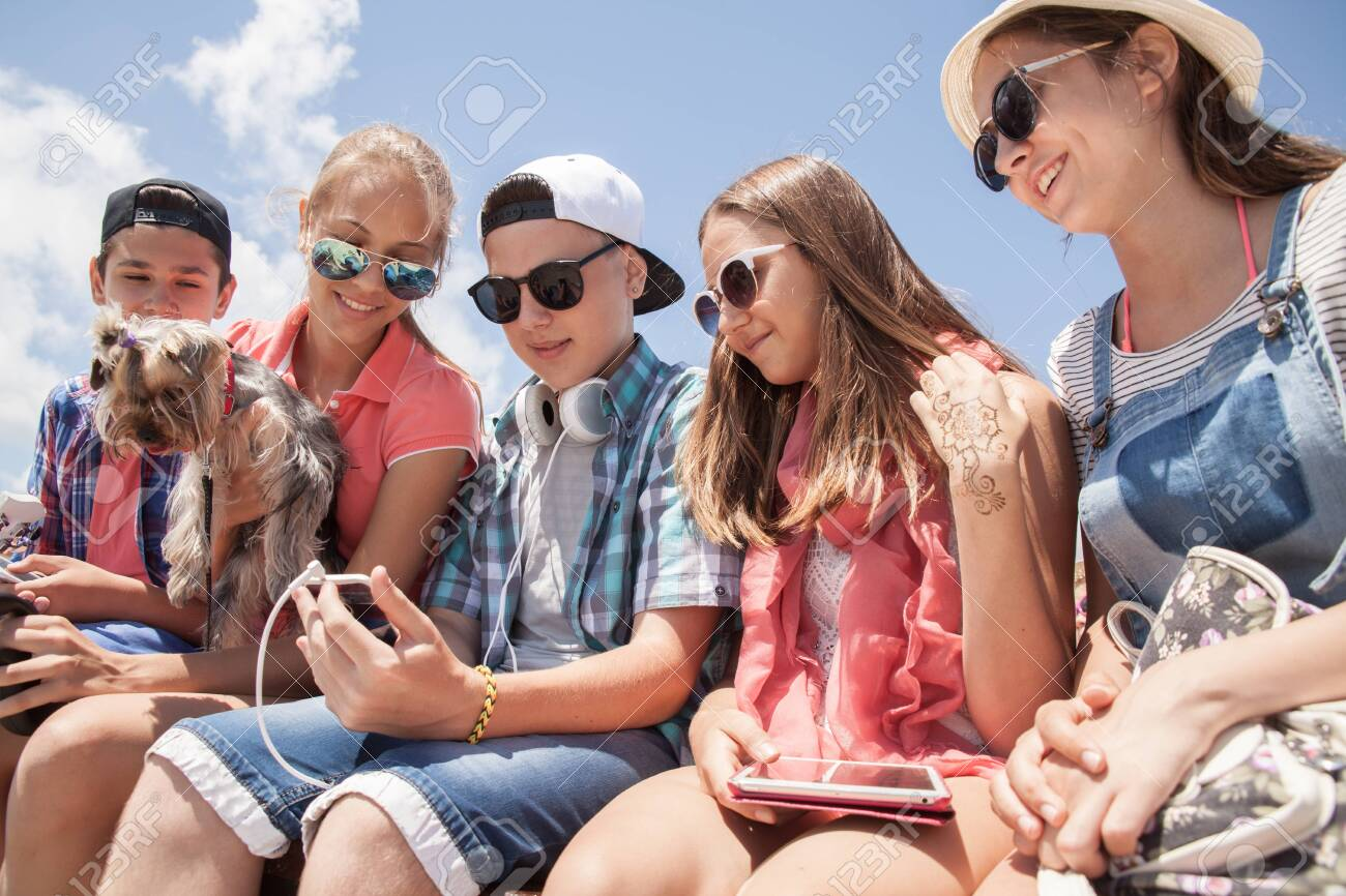 group of teenagers spending time together with gadgets - 130485914