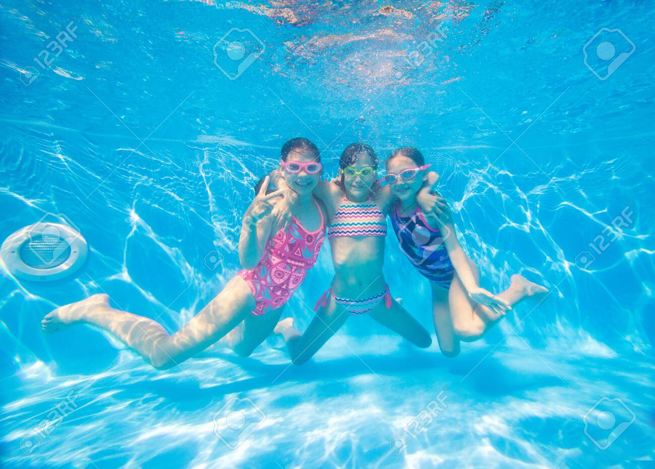 group of little girls swimming in pool underwater. - 130478244