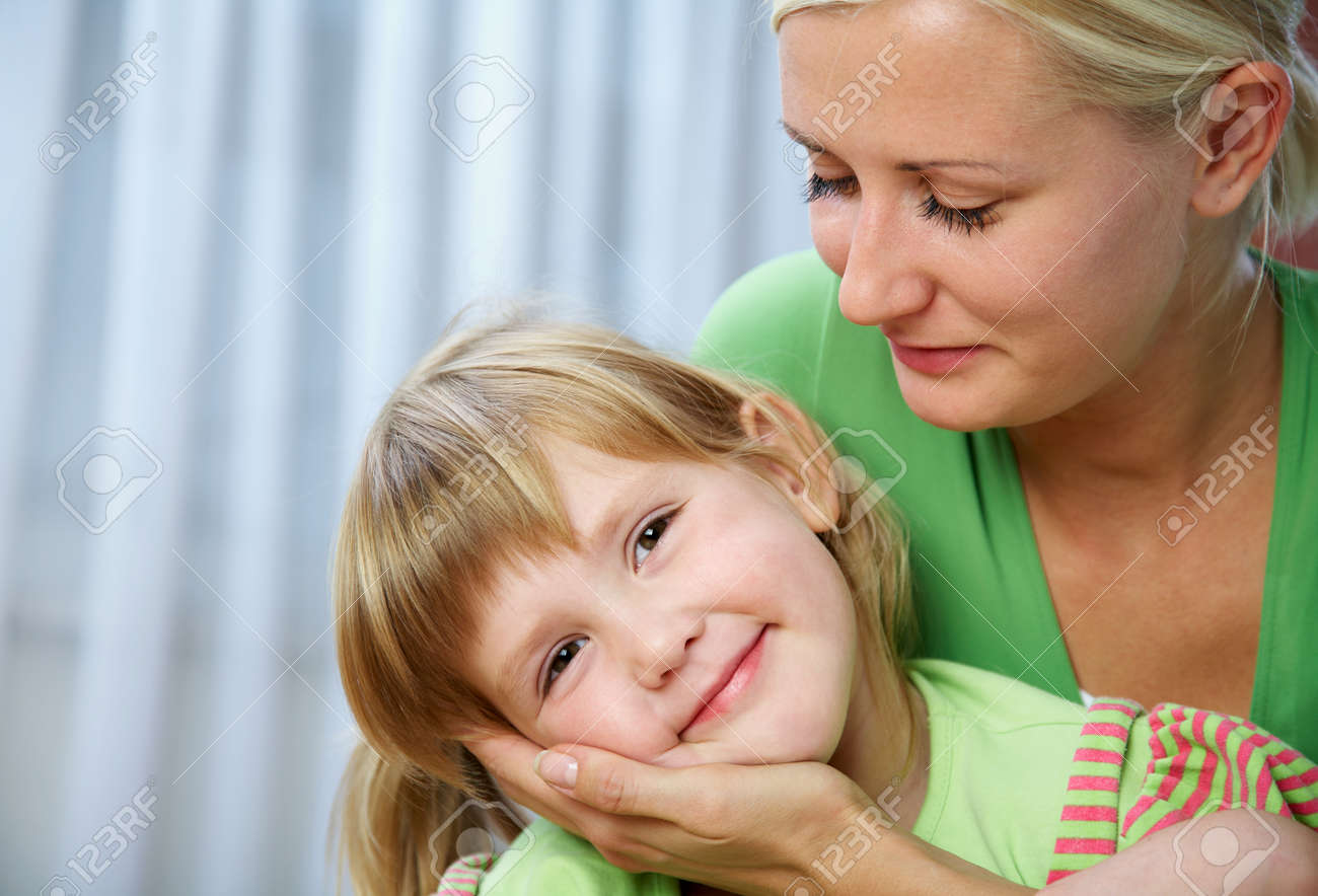 Young blonde mom tenderly hugs her little daughter at home. - 166042504