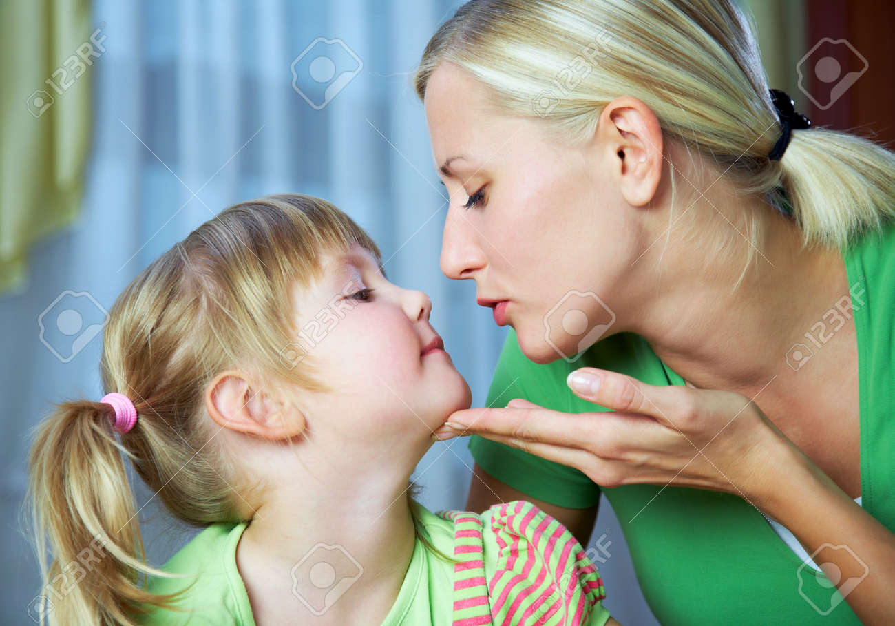 Young blonde mother gently kisses her little daughter at home - 166042505