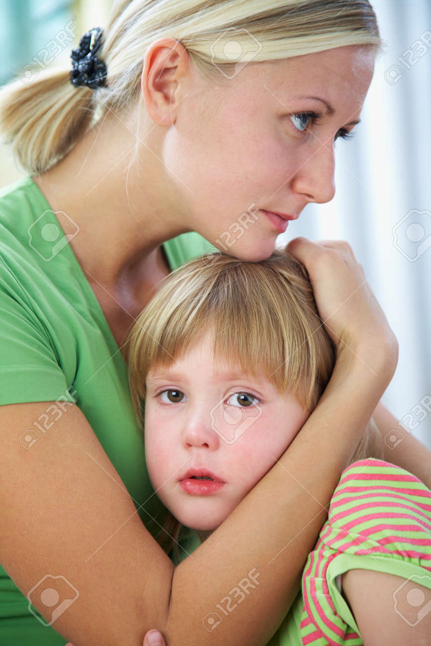 Young blonde mom tenderly hugs her little crying daughter at home. - 166042509