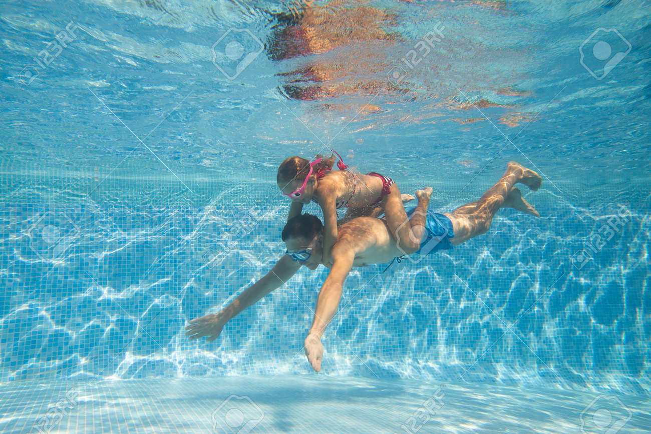 underwater photo of young dad with little girl in swimming pool - 166194606