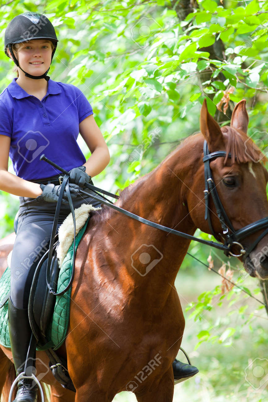 Portrait of young horsewoman on red horse - 166657701