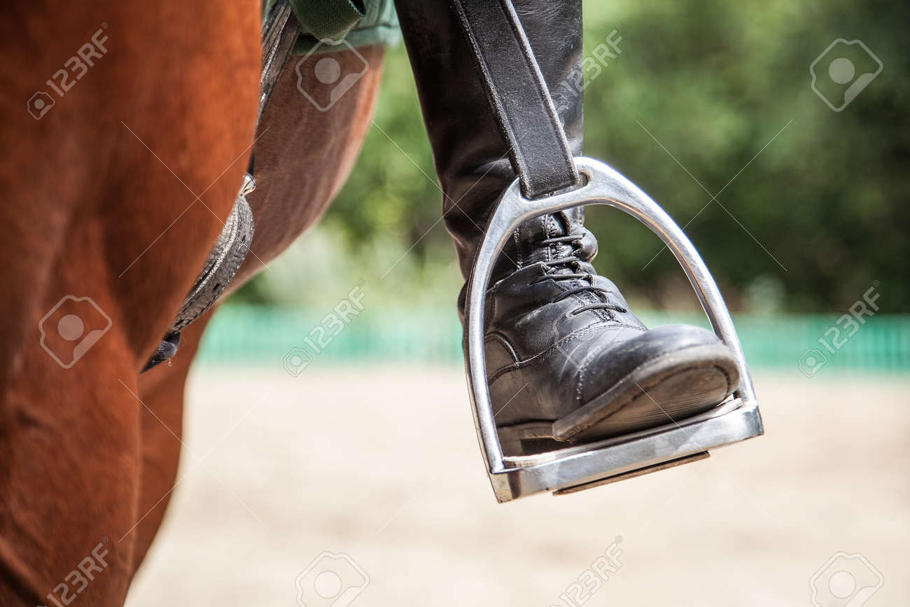 close-up of a rider's leg on a stirrup on a horse - 166657062