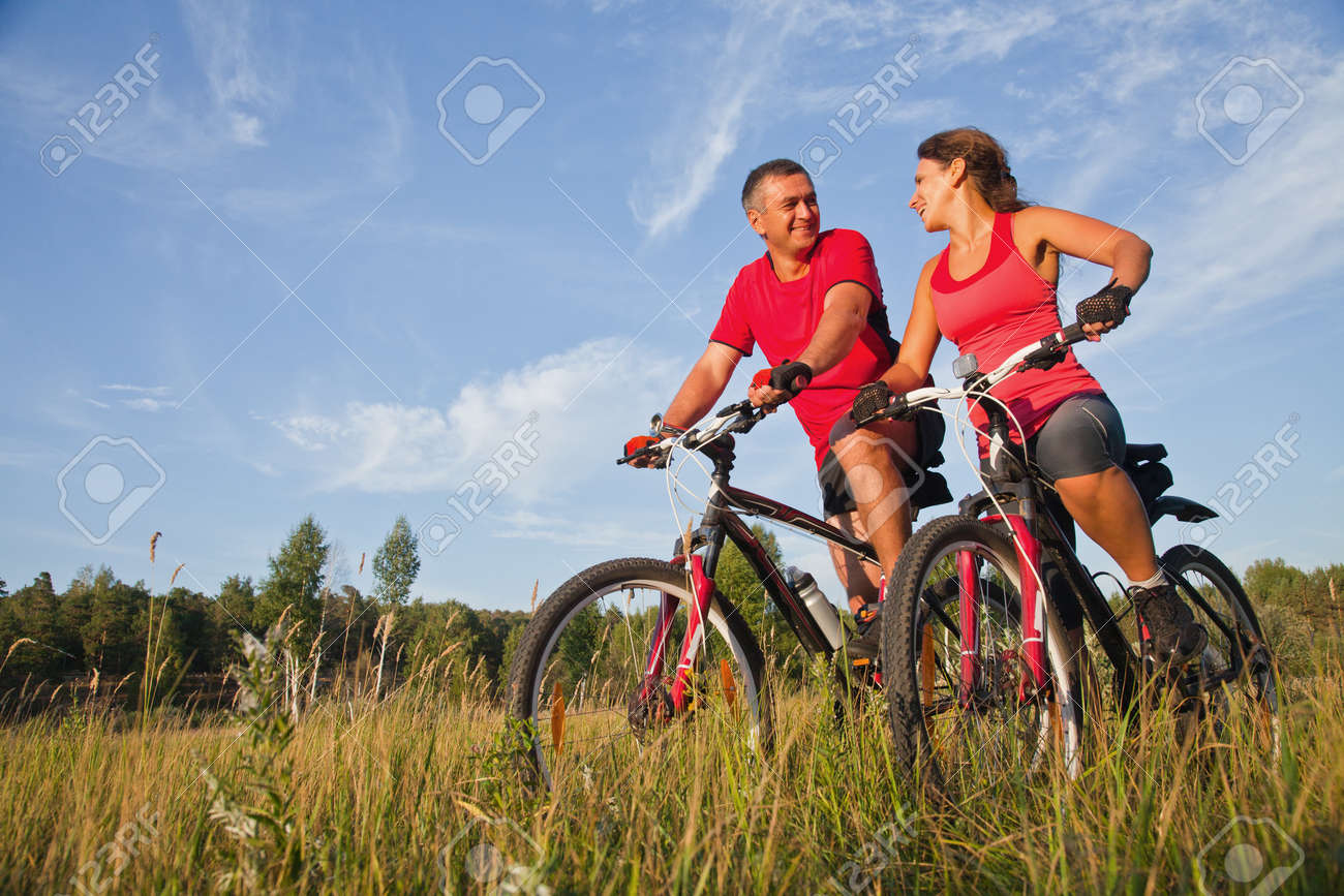 happy mature couple riding a bicycle in the green park - 167488327