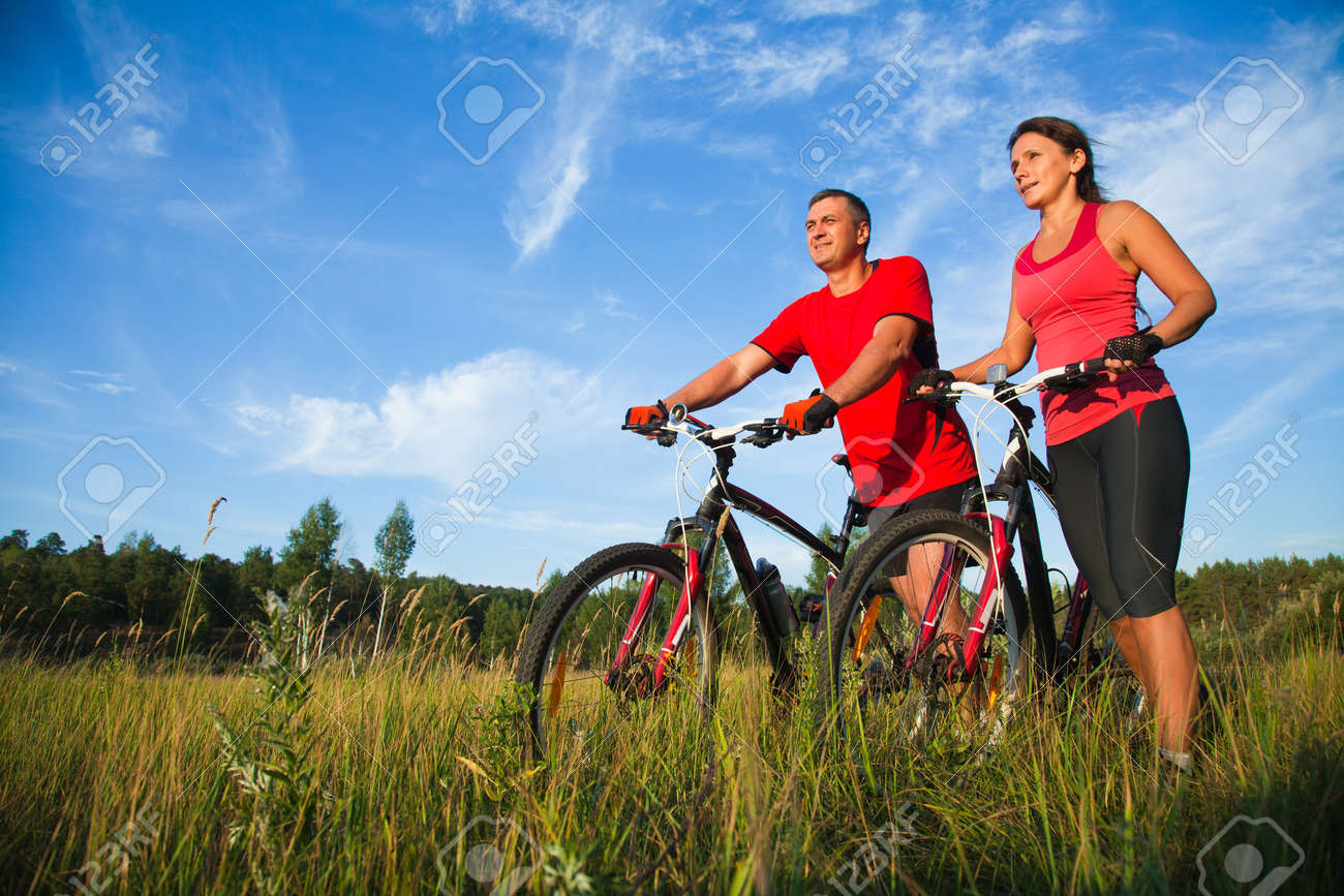 happy mature couple riding a bicycle in the green park - 167488432