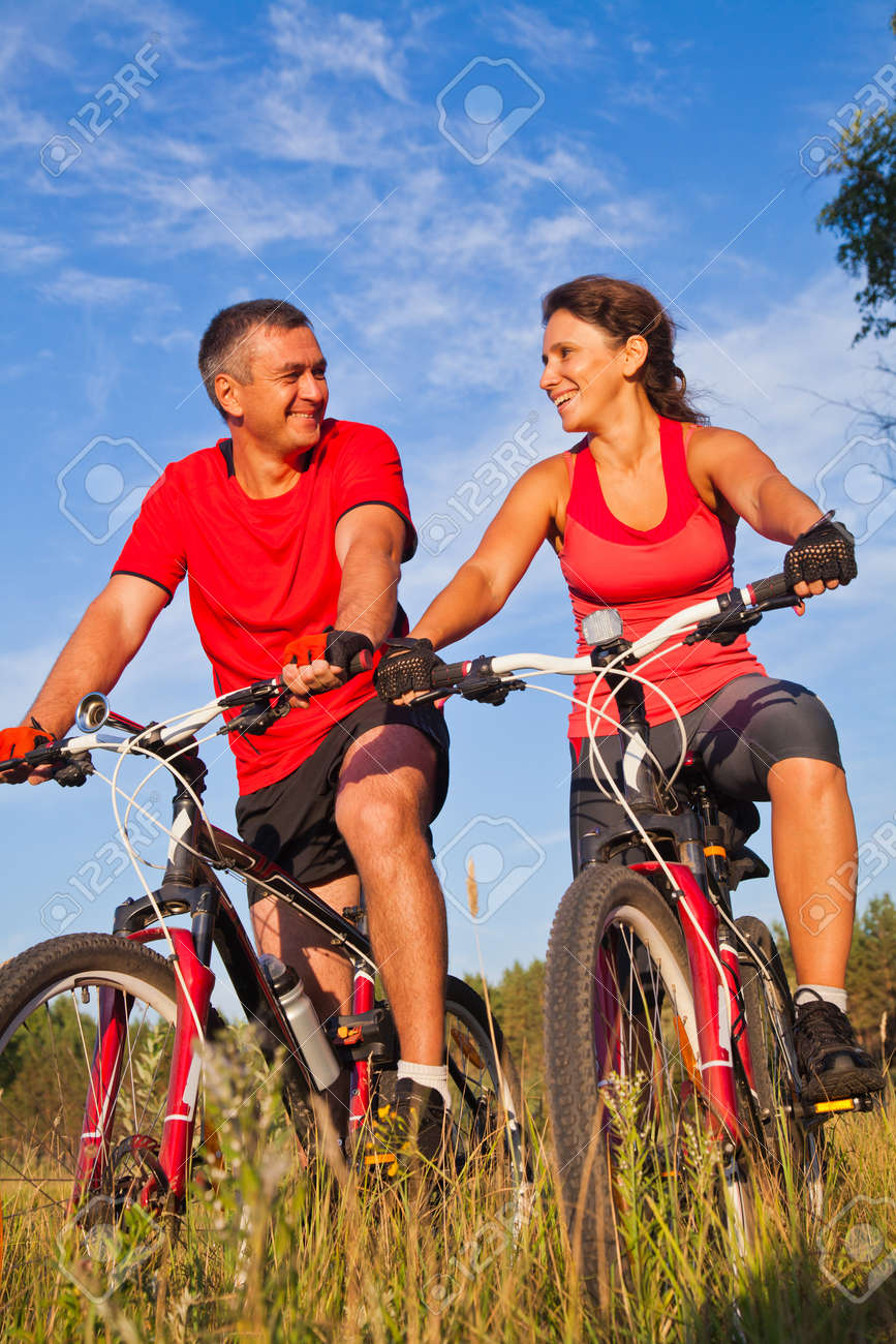 happy mature couple riding a bicycle in the green park - 167908279