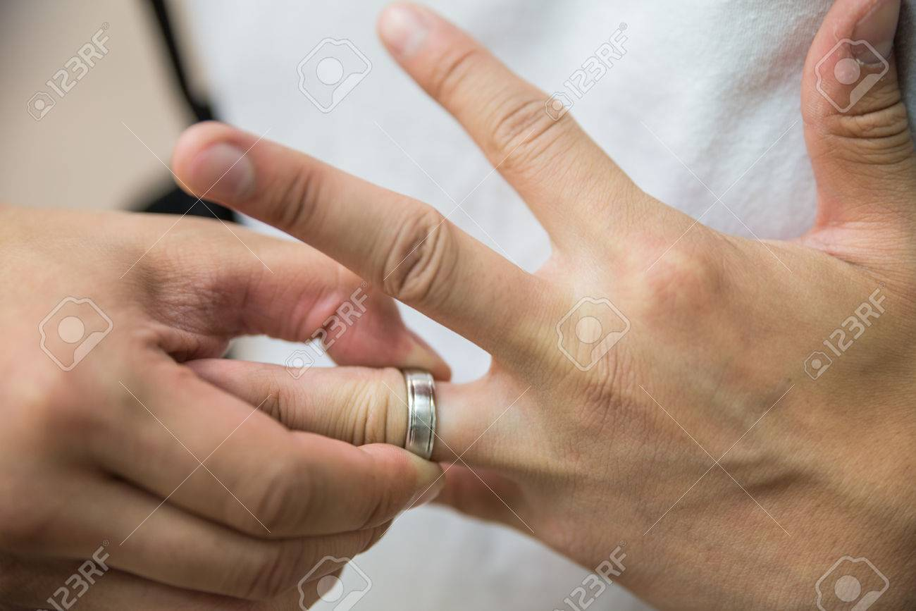 Man Pulling A Wedding Ring Off From His Finger Stock Photo Picture