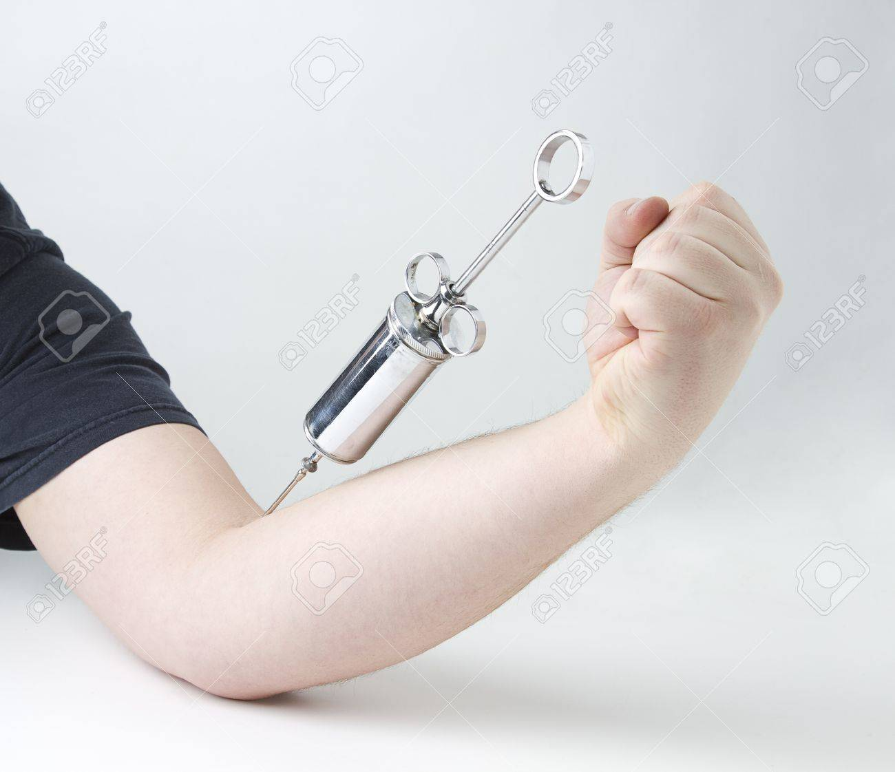 metal syringe in male arm against white background Stock Photo - 8800598