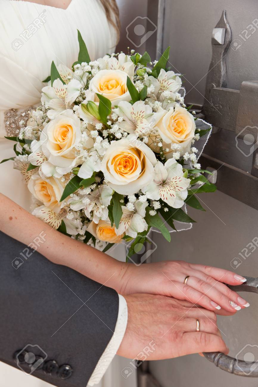 Wedding bouquet and hands of a newly-married couple Stock Photo - 10649082