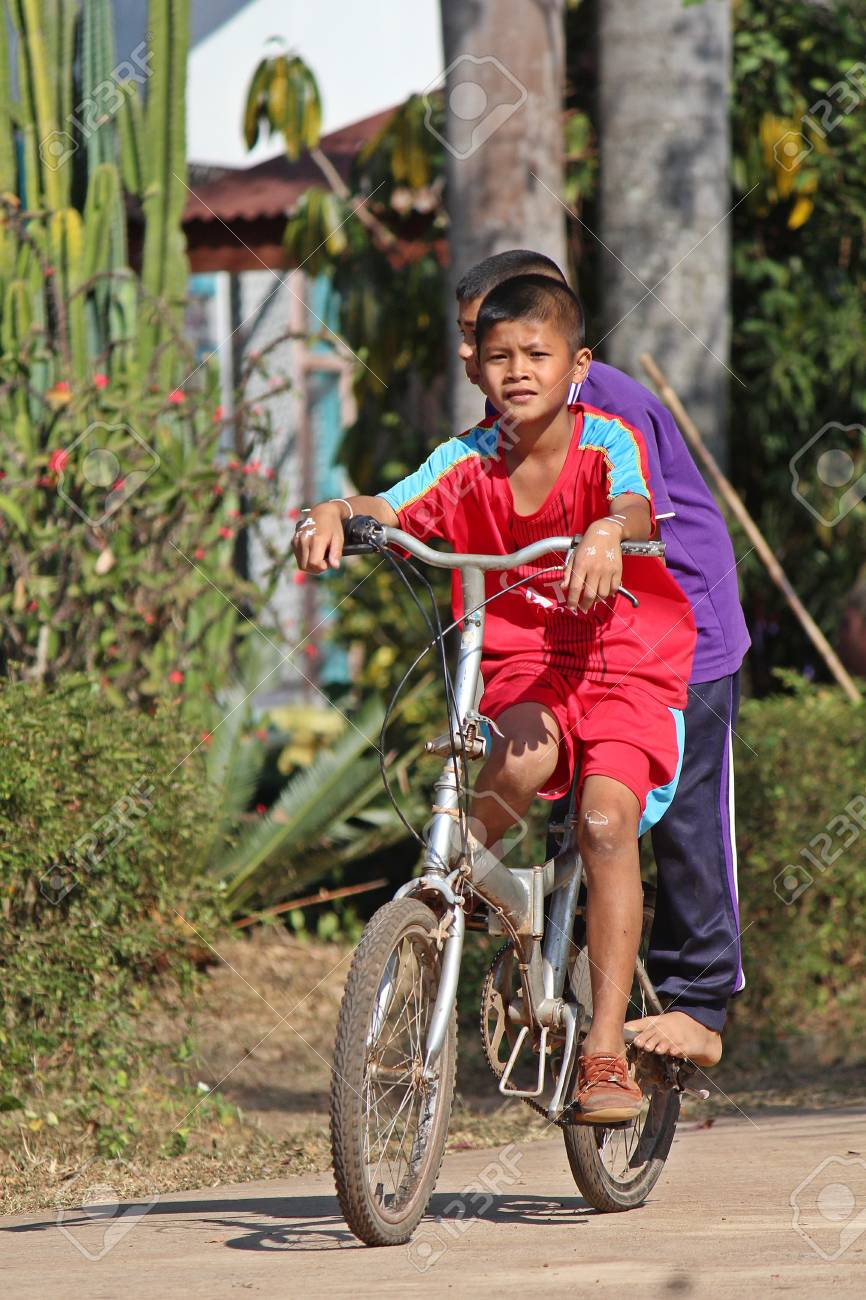 1769d060e84 Stock Photo - UDONTHANI, THAILAND – FEBRUARY 1, 2019 : Two Asian boys, they  are riding bicycle in front of school building, they will be getting back  to ...