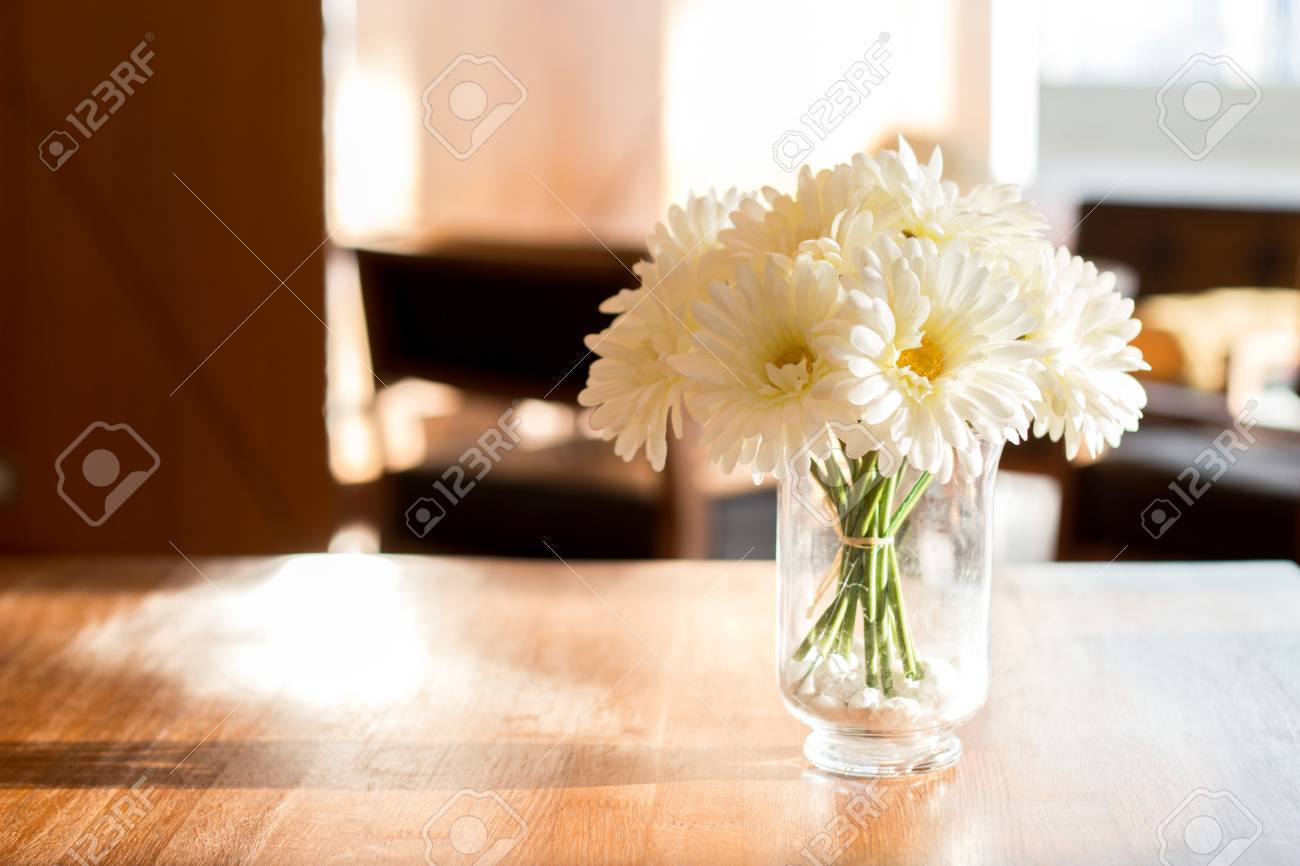 Close Up White Artificial Daisy Flower In Wase On Wood Table Stock