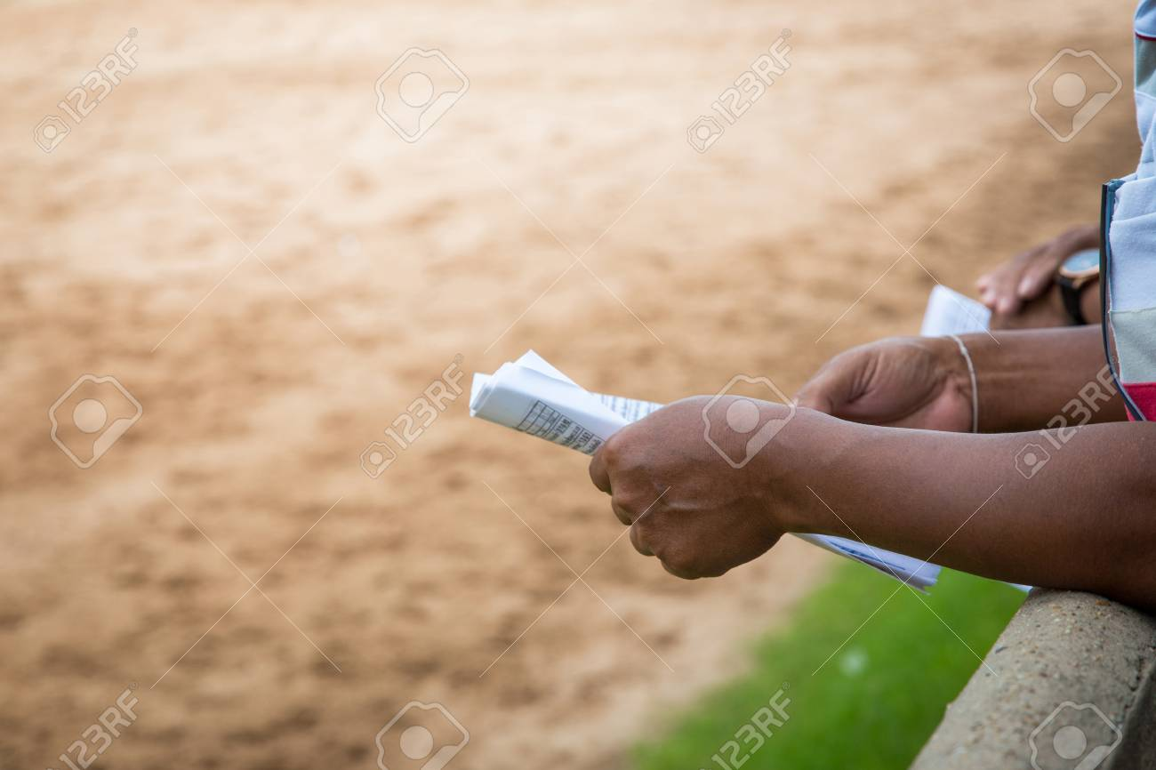 close up hand hold table of bet data for horse racing game