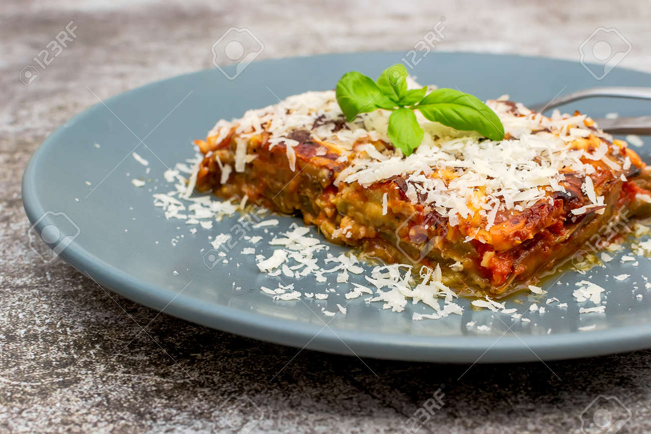 Parmigiana di Melanzane - strips of fried eggplant with parmesan, baked in tomato sauce in a ceramic pan - 157152549