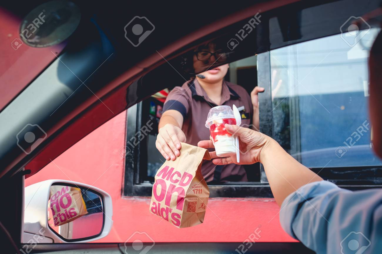 Bangkok, Thailand - Mar 4, 2017: Unidentified customer receiving hamburger and ice cream after order and buy it from McDonald's drive thru service, McDonald's is an American fast food restaurant chain - 92694002