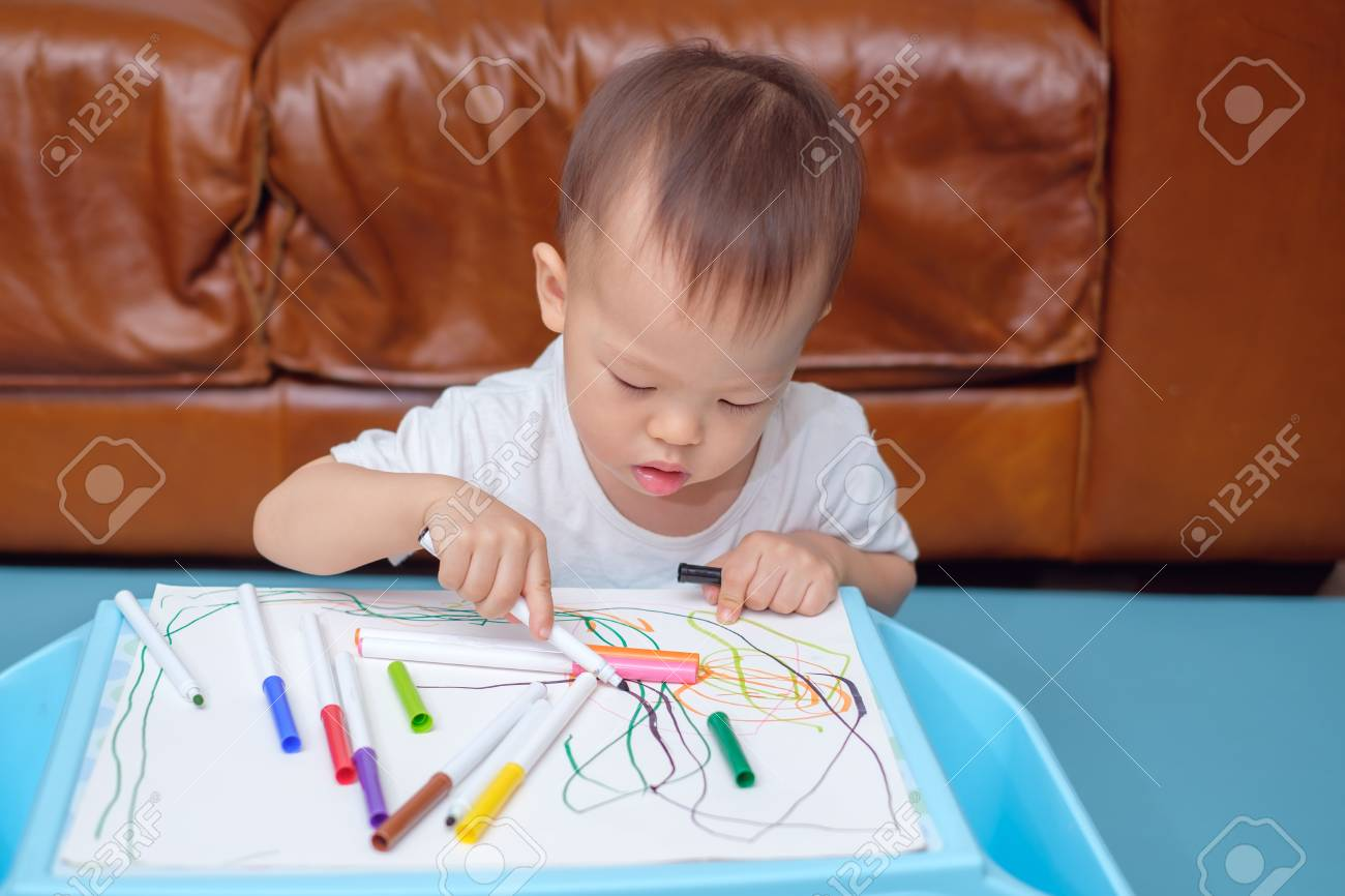 Cute little Asian 18 months / 1 year old toddler boy child drawing,  scribbling with