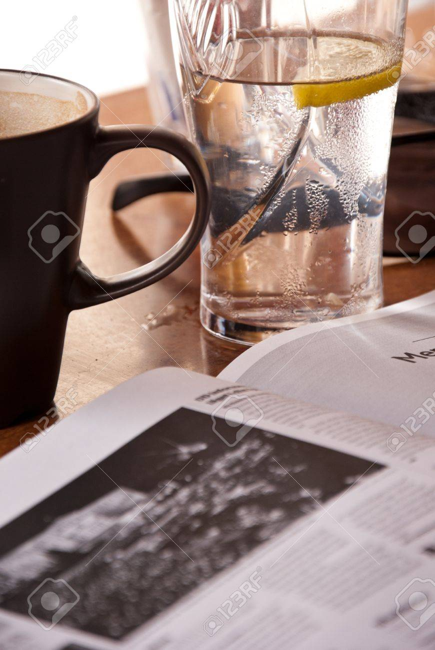 Reading newspaper in coffee-house during break  On the table
