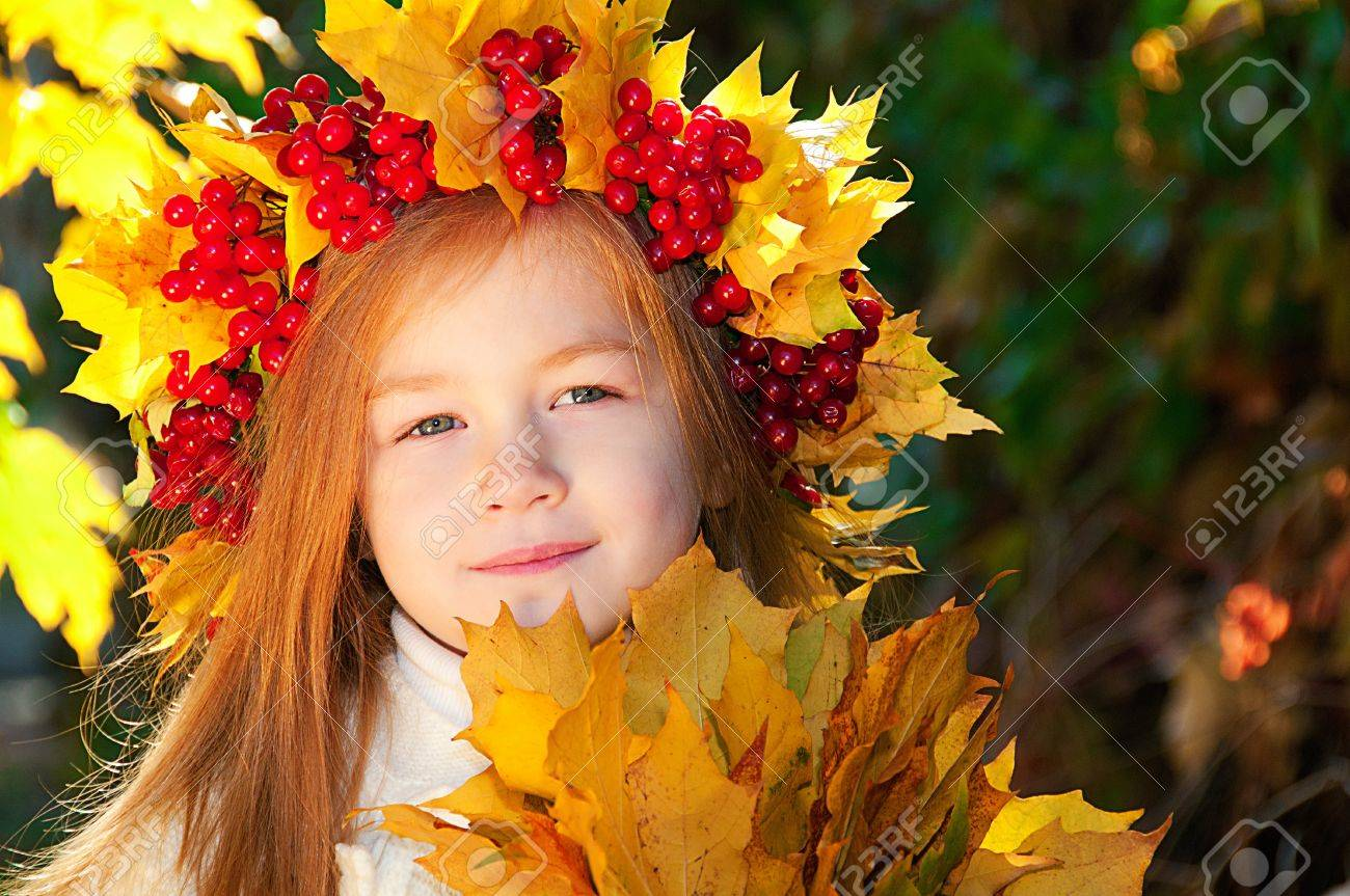 Cute smiling girl in a wreath of red viburnum on the head and with a bouquet of maple leaves in the hands Stock Photo - 11733516