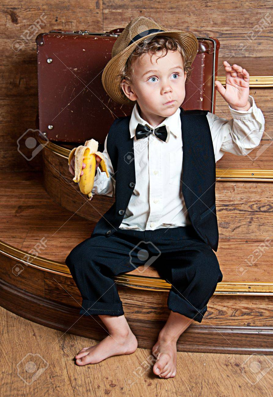 Cute little boy with a banana in his hand sitting on the steps  Photo of retro style Stock Photo - 13181982