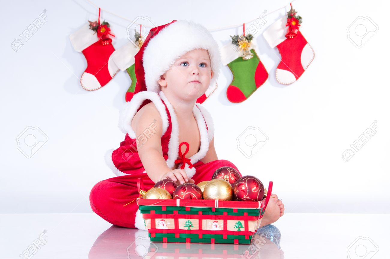 Cute baby Santa Claus with garlands and a basket of Christmas toys Stock Photo - 15675696