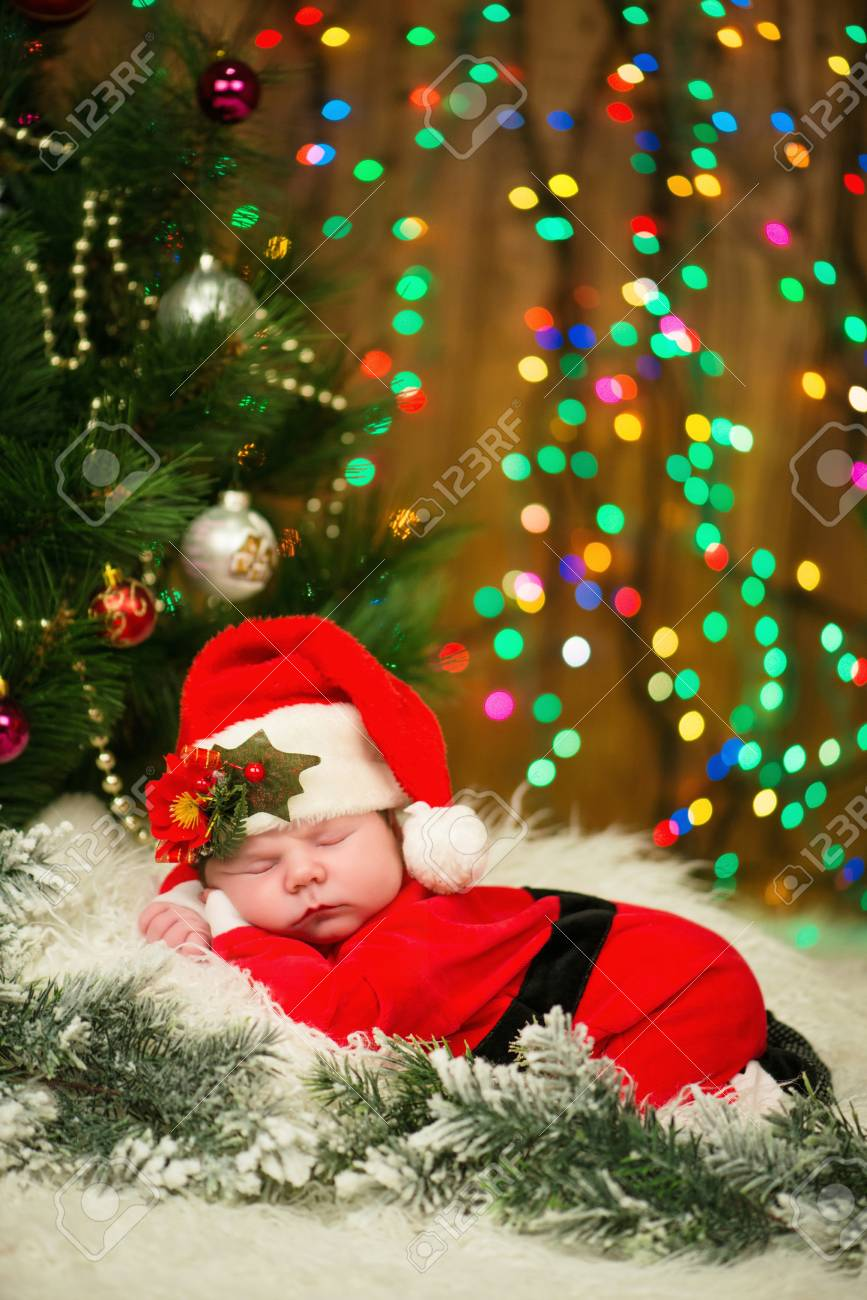 Portrait of newborn baby boy in santa clothes lying under christmas tree stock photo 66948104