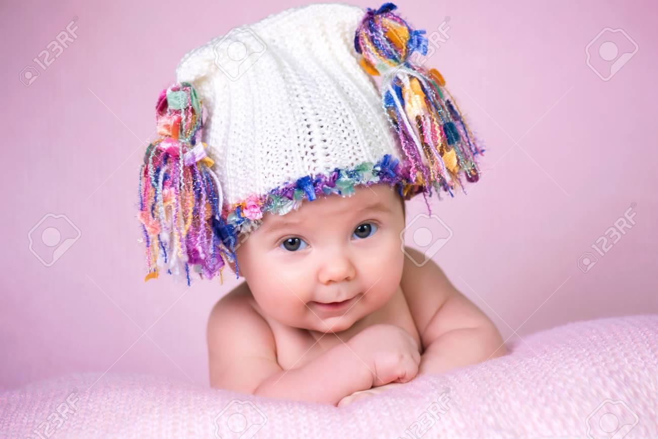 07ba71571 Bebé niña hermosa que lleva gorro de lana de color rosa. Foto de archivo -