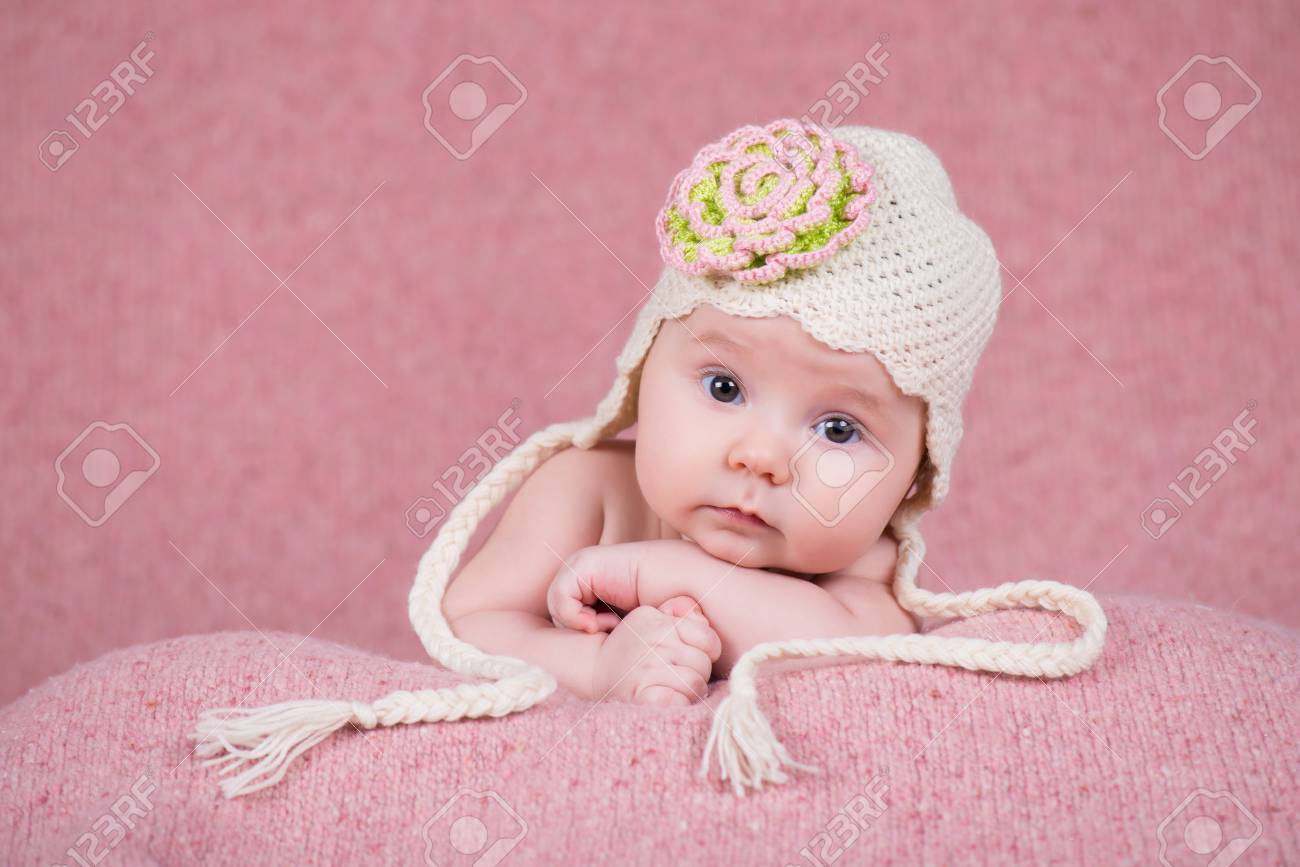 8604ca3bf21 Newborn girl in warm knitted hat with a flower Stock Photo - 71018884