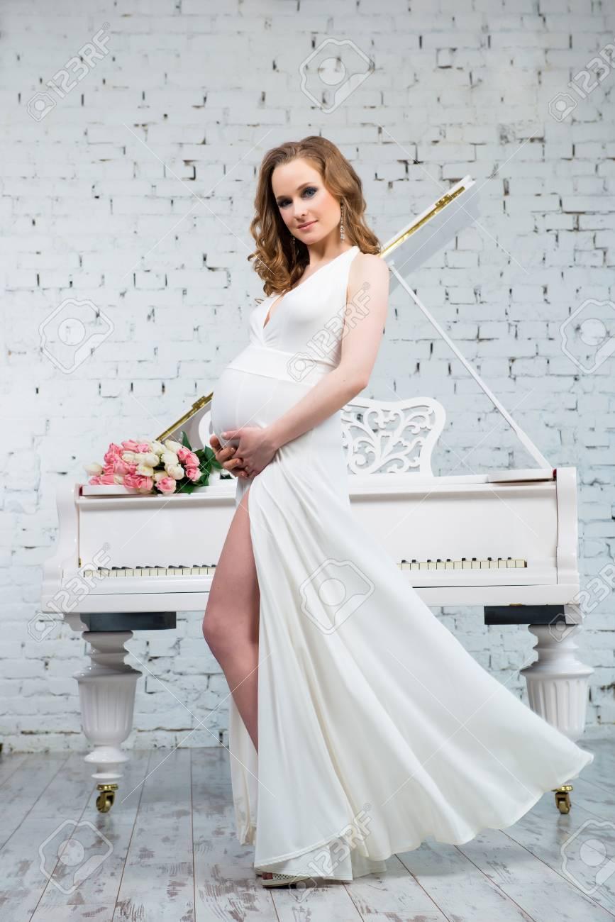 venta de tienda outlet gran variedad de estilos Nuevos objetos Mujer embarazada elegante con un vestido blanco clásico cerca del piano  blanco