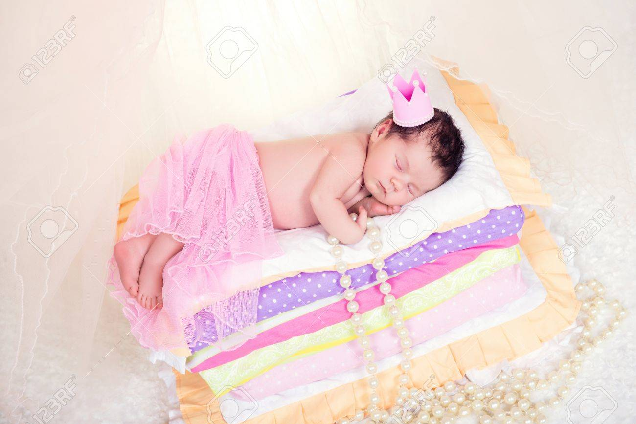 Newborn Baby Girl In A Crown Sleeping On The Bed Of Mattresses