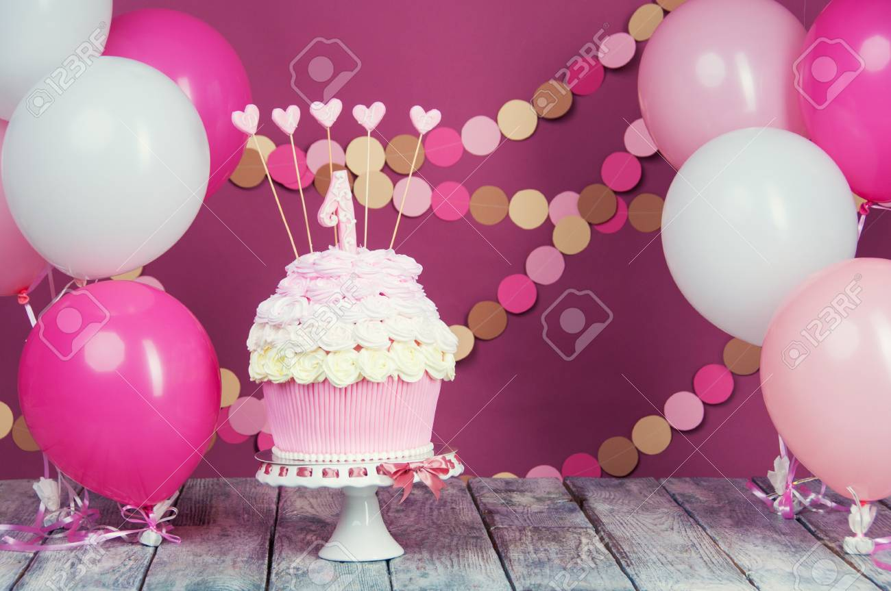 First Birthday Cake With A Unit On Pink Background Balls And Paper Garland Stock