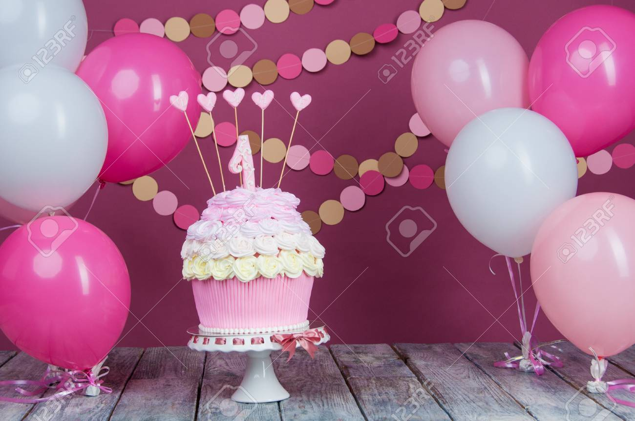 First Birthday Cake With A Unit On A Pink Background With Balls