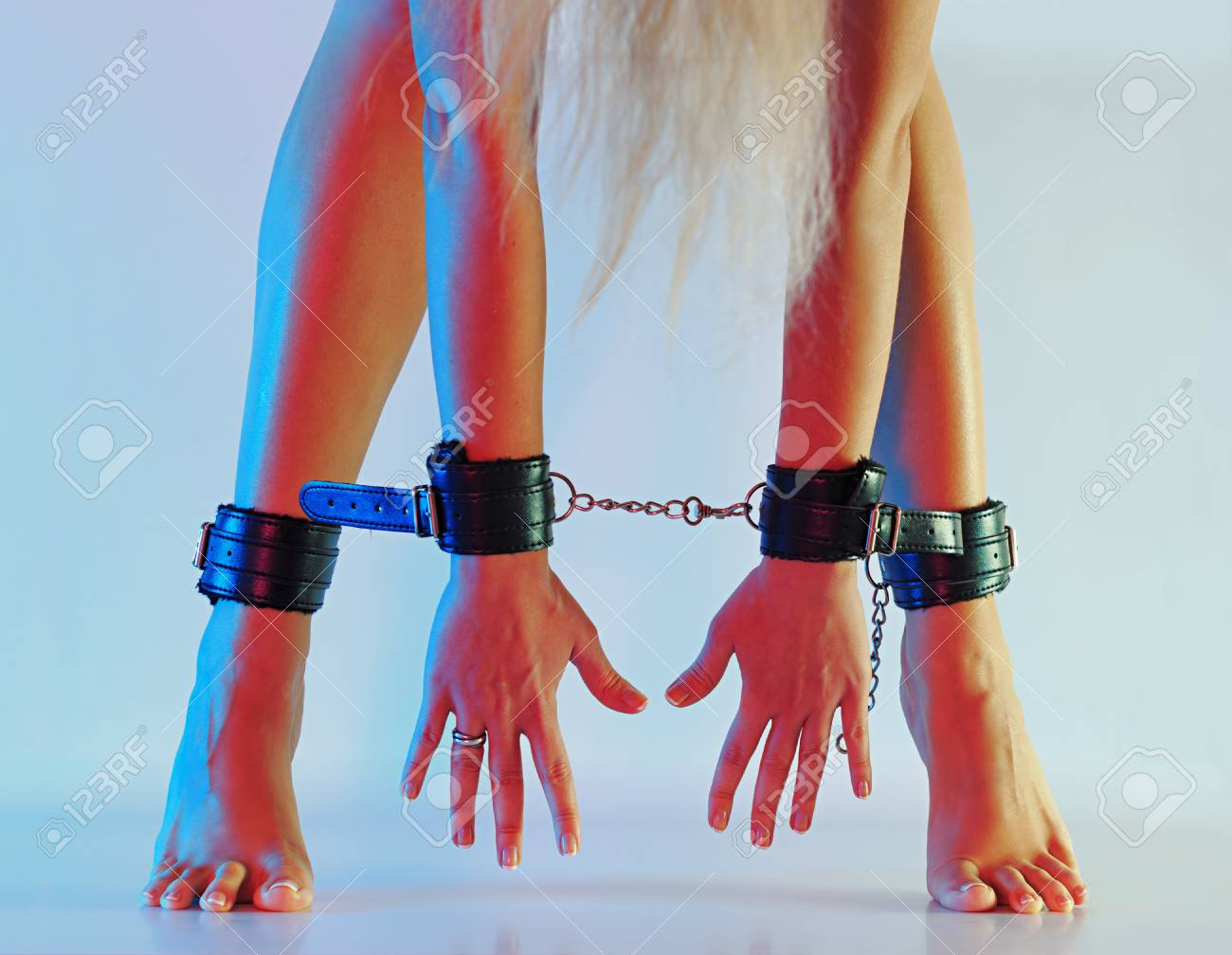 Sexy Long Female Legs Barefoot On Tip Toes In Leather Cuffs Chained Together With Hands