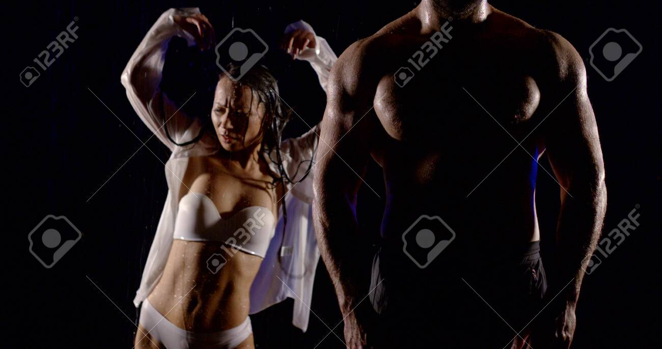 Young couple dancing in the rain on a dark background. Wet brunette girl in white shirt and white underwear and silhouette of muscular tall man with torso. - 129272796