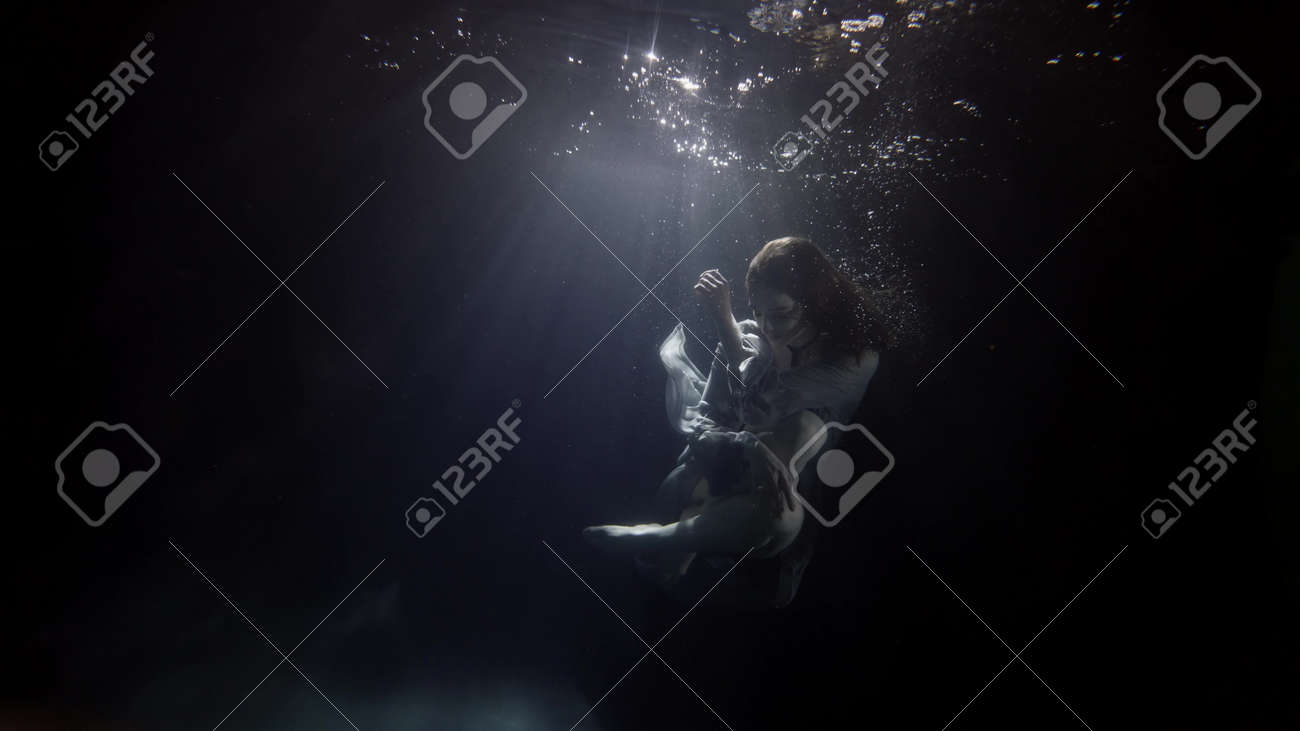 fragile and graceful woman is floating in dark water of swimming pool, mysterious subaquatic shot - 167450616