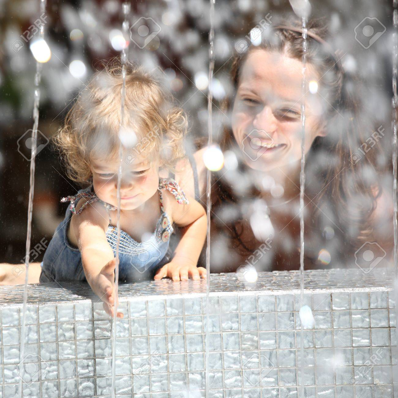 Smiling child and woman in fountain splashes Stock Photo - 8786135