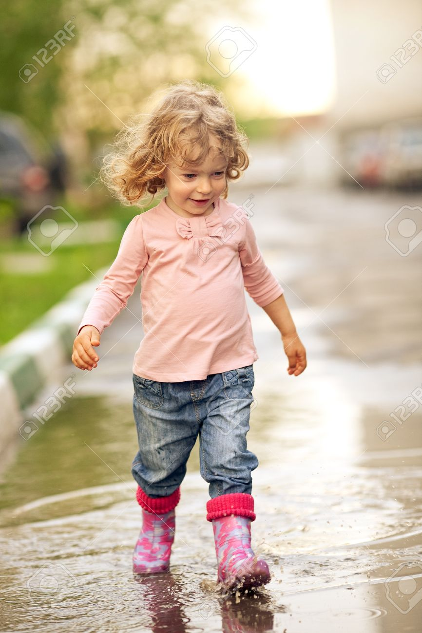 cute child walking on puddle in autumn stock photo picture and