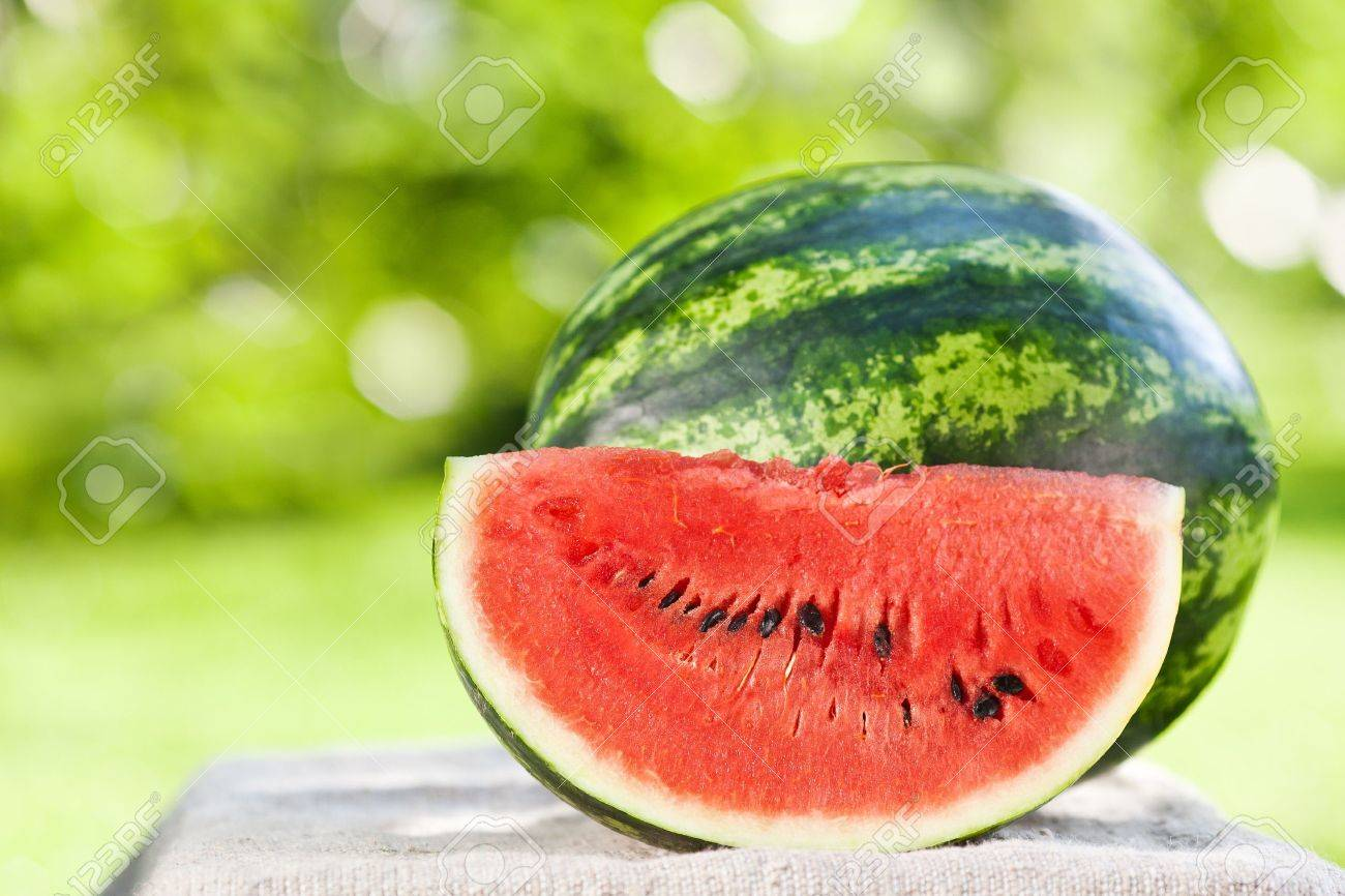 Fresh juicy watermelon against natural green background in spring park Stock Photo - 11936397