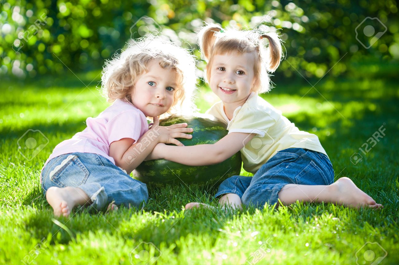 Happy children playing with watermelon in spring park Stock Photo - 12235380