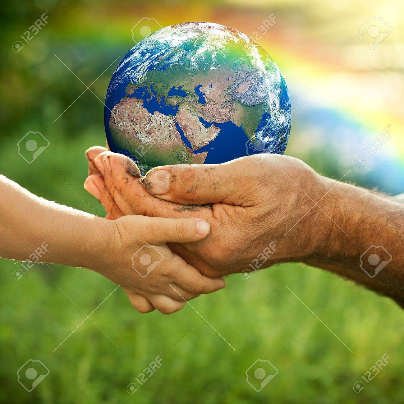 Hands of senior man and baby holding Earth against a rainbow in spring Ecology concept - 12580809