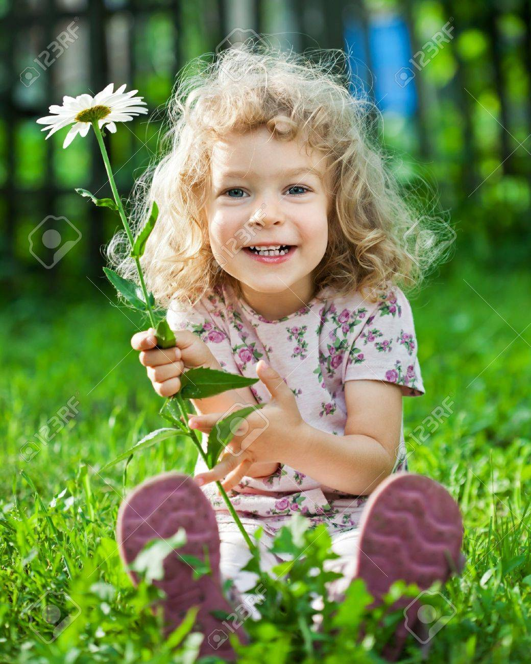 Happy smiling child with flower sitting on green grass outdoors in spring garden Stock Photo - 12580805