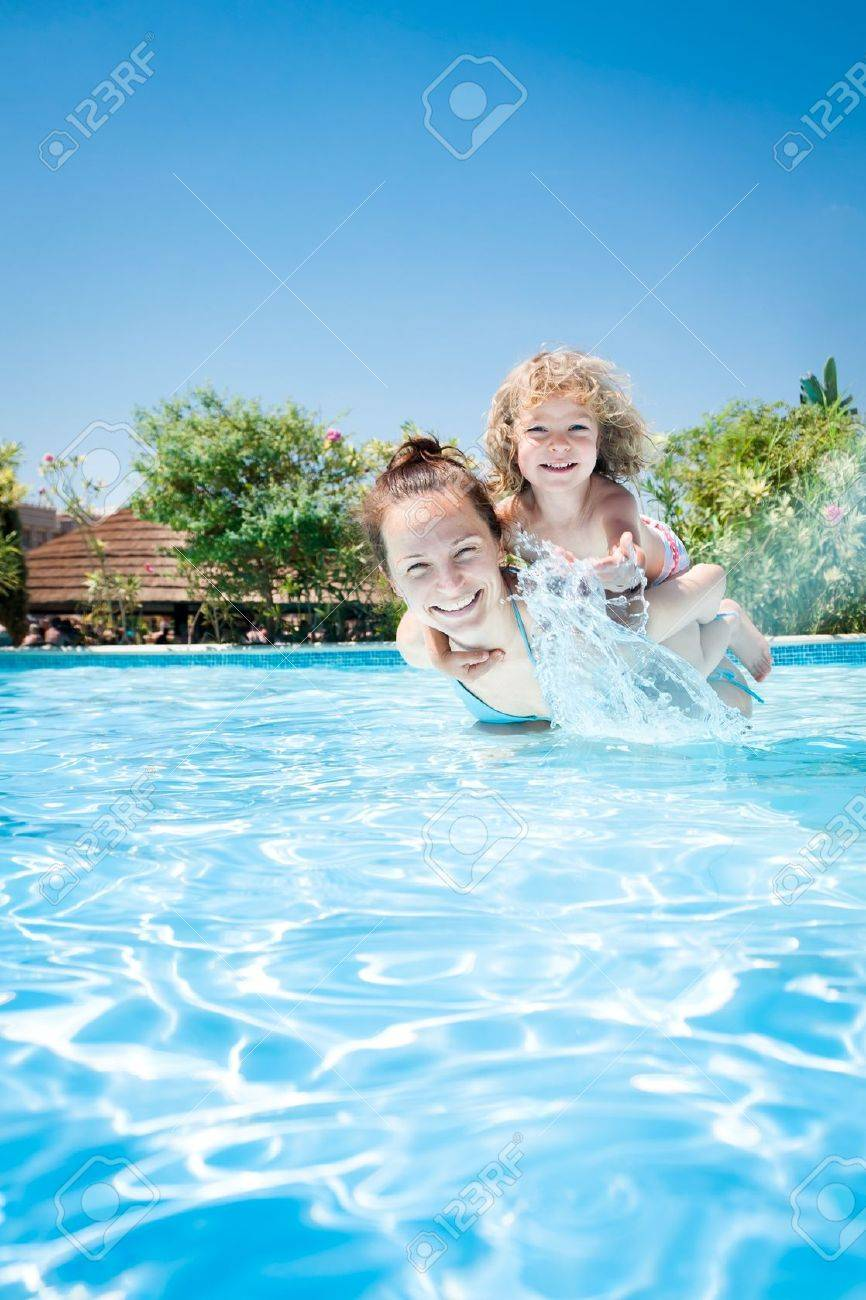 Happy kid playing with woman in swimming pool on a tropical resort at the sea  Summer vacations Stock Photo - 12925295