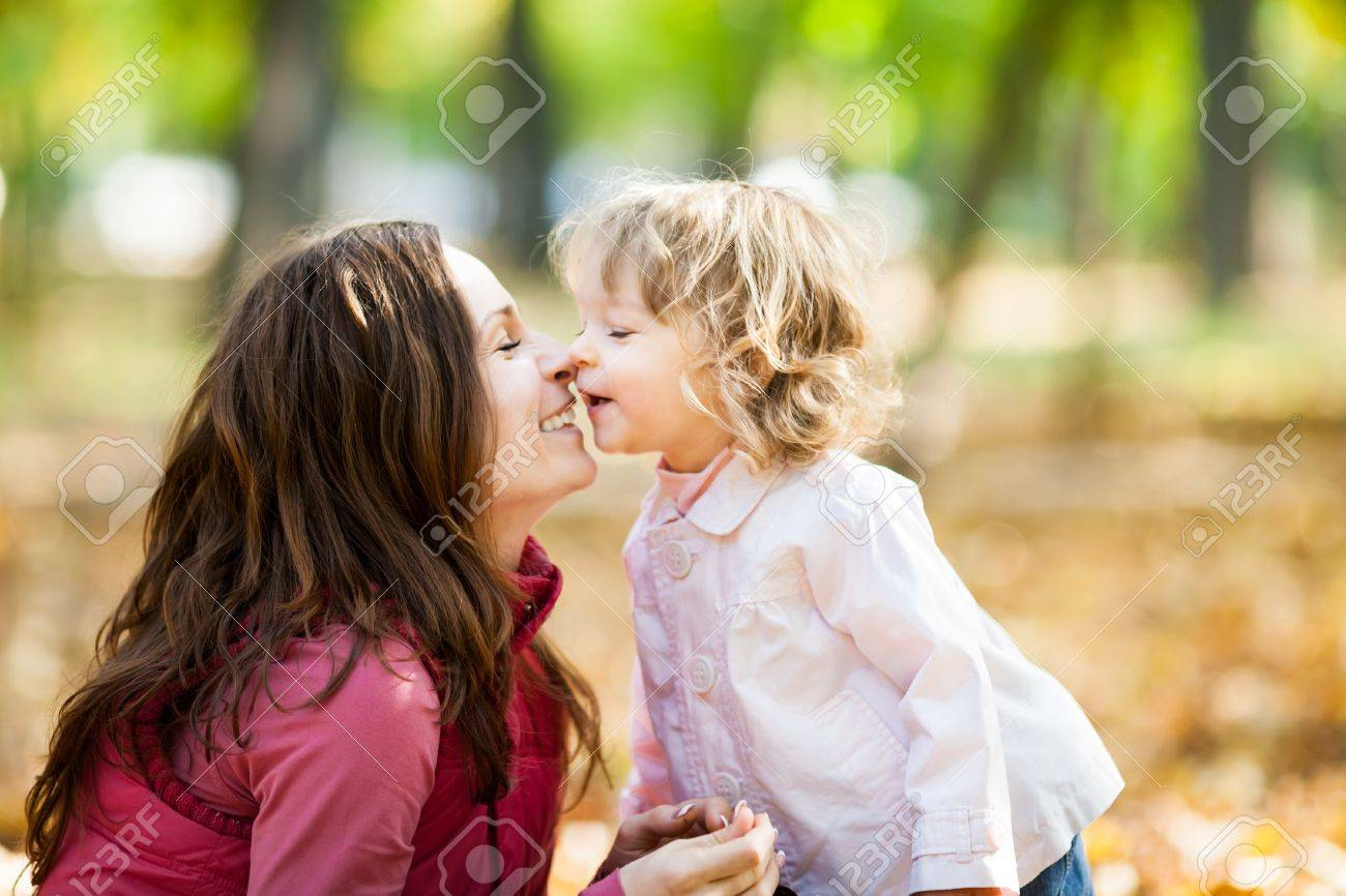 Happy smiling family playing against blurred autumn leaves background Stock Photo - 13881483