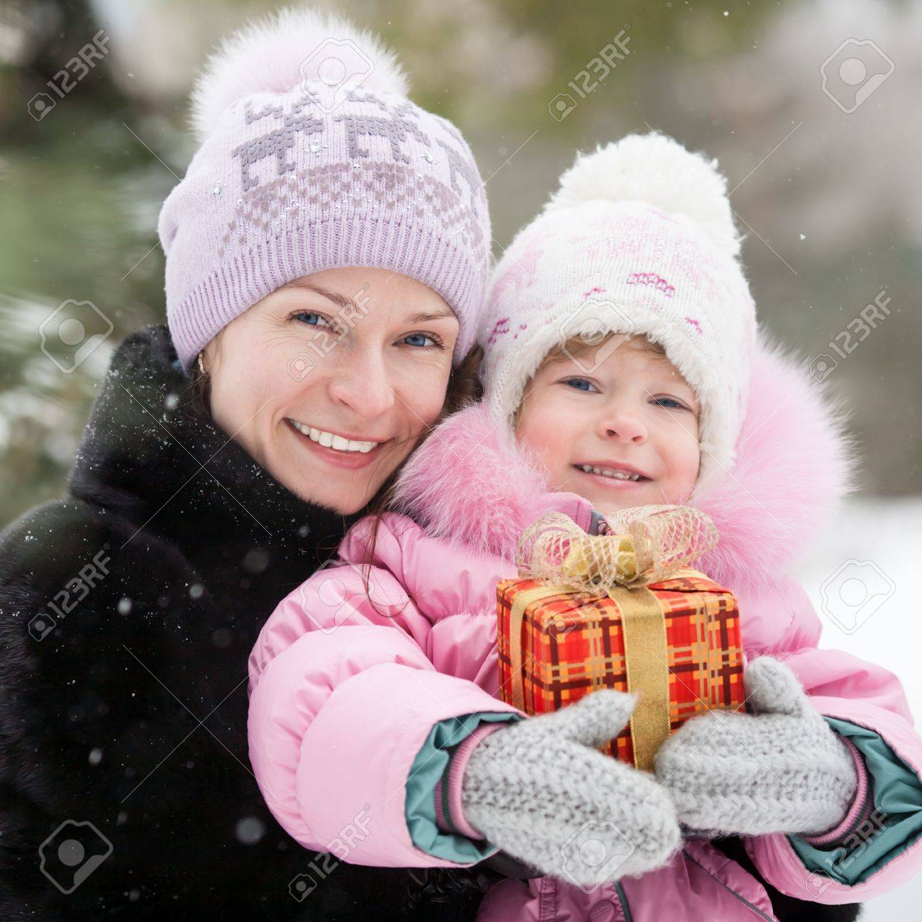 Happy family with Christmas gift box in winter park Stock Photo - 14976315