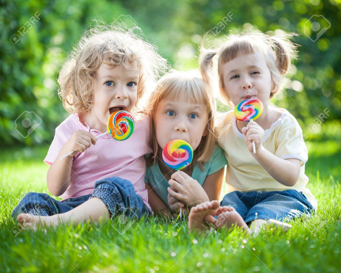 Group of happy children sitting on green grass in spring park Stock Photo - 17241957