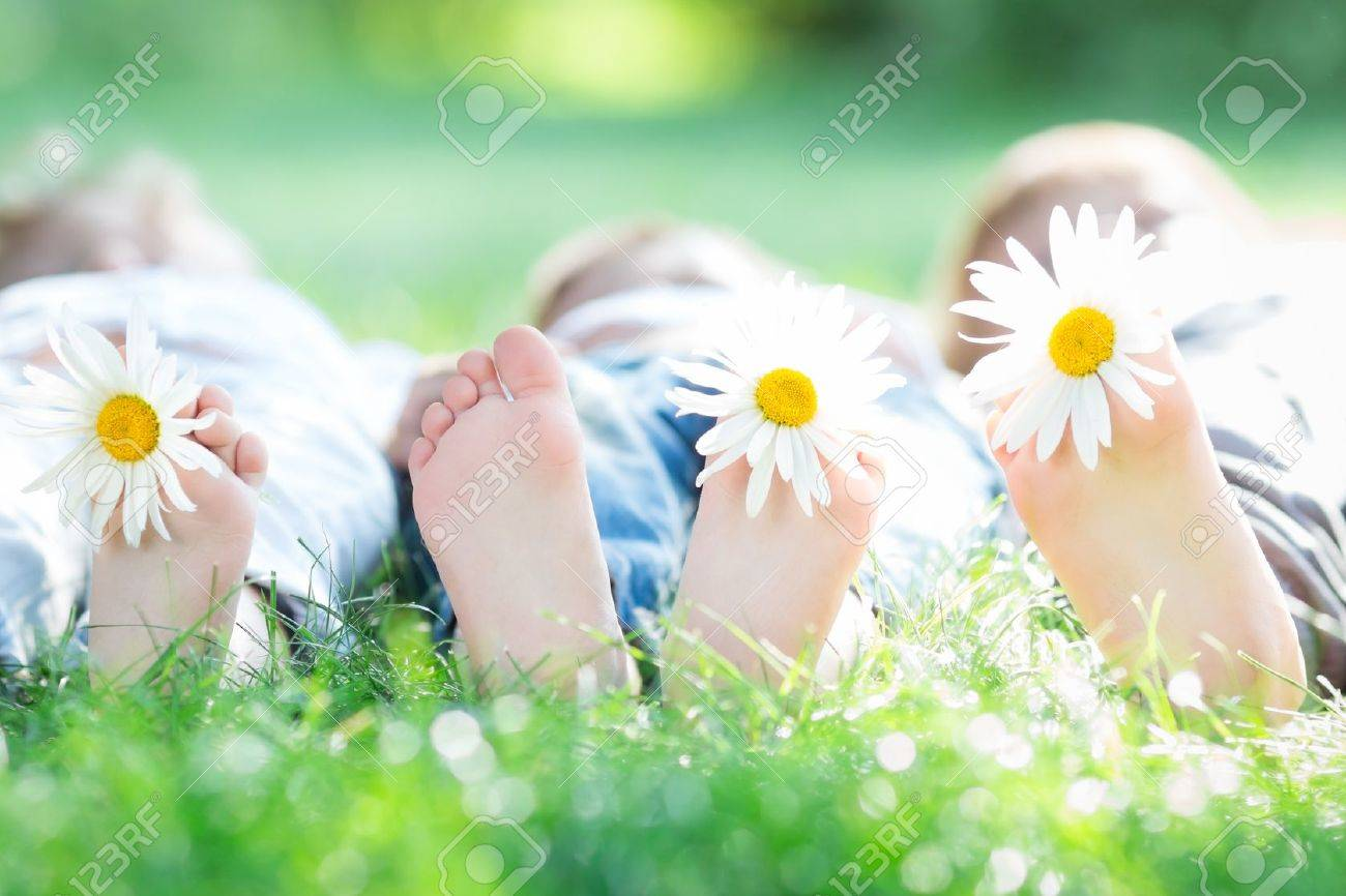 group of happy children lying outdoors against green spring background stock photo 17348111 - Spring Pictures For Children